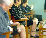 a group of elderly people having their legs treated