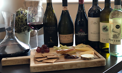 a cheese platter with various bottles of wine behind it