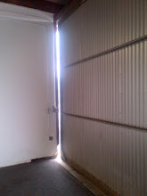 Photo: East side door to hangar gap.  Need to replace wall trim with Trex, and add gap seal.