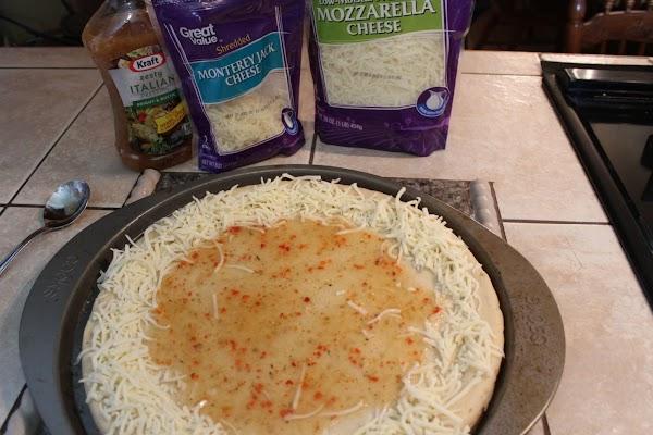 Ladle dressing on pizza for the sauce.  Arrange Monterey Jack cheese around edge...