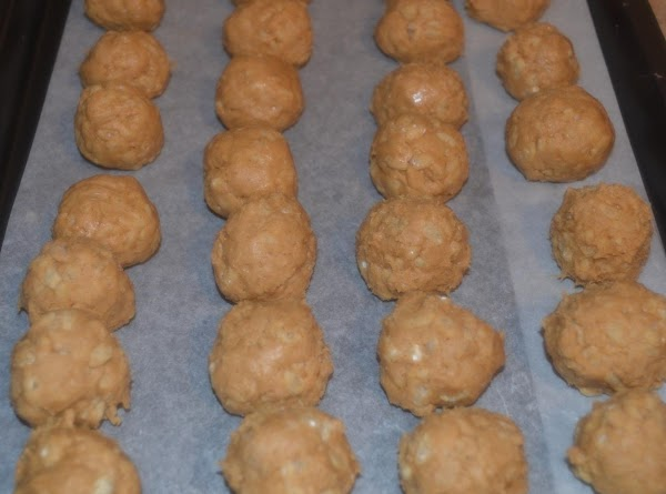 Line a large cookie sheet with parchment paper.  Form chilled peanut butter mixture...