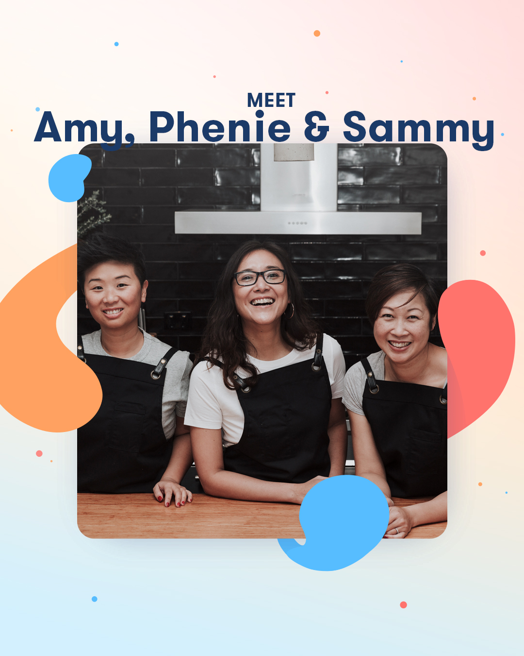 Amy, Phenie and Sammy all wearing white shirts and black aprons, smiling in a kitchen with a black tile wall.