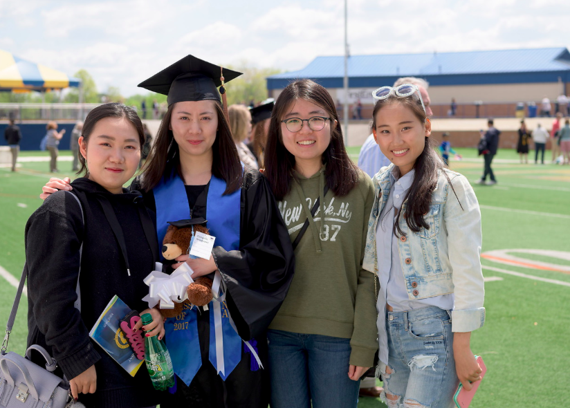 A Kent State graduate poses with her family  after a previous commencement ceremony.