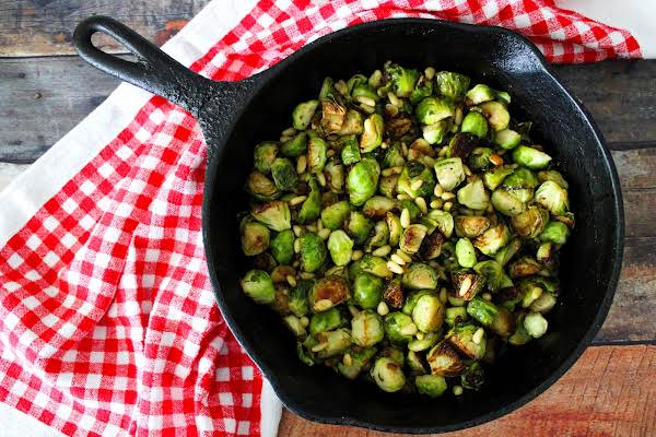Sauteed Brussels Sprouts With Pinion Nuts In A Cast Iron Skillet.
