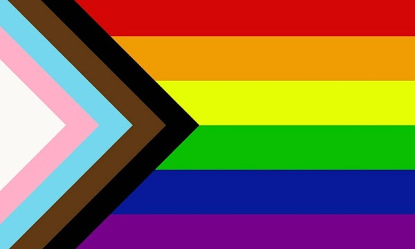 The newer LGBTQ+ flag design that includes black, brown, pink, white and blue stripes in a right angle pointing to the center of the rainbow flag.