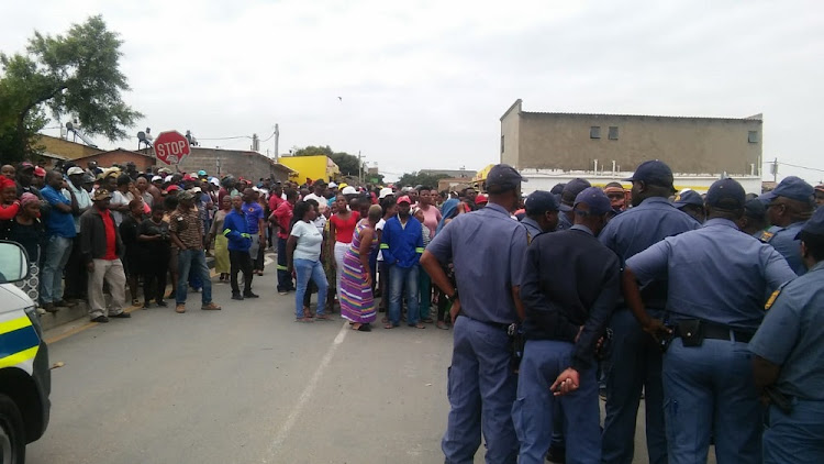 Police listen to the angry residents who are complaining that they are being removed from RDP houses as they are accused of being foreigners.