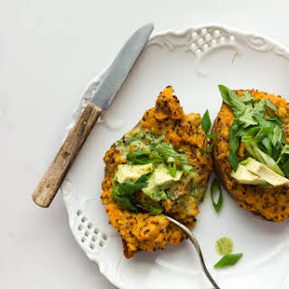 STUFFED SWEET POTATOES WITH CURRIED QUINOA + AVOCADO CILANTRO SAUCE.