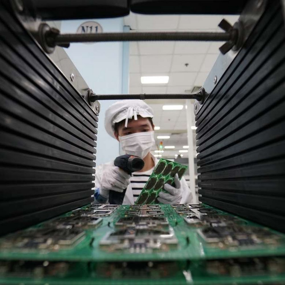 A technician stands inspects a motherboard