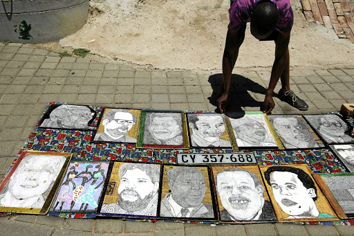 Mthokozisi Dyantyi, 31, sells the paintings of SA's Struggle heroes in Vilakazi Street, Orlando West, Soweto before the start of the ANC elective conference in Nasrec tomorrow. / SANDILE NDLOVU