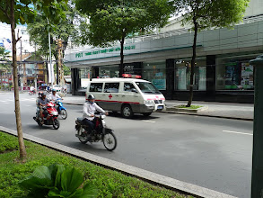 Photo: Saigon - ambulance which you can see very often, very low wires belov 2m height, in front of school, traffic, typical restaurant w plastic chairs, lunchtime/siesta and bride