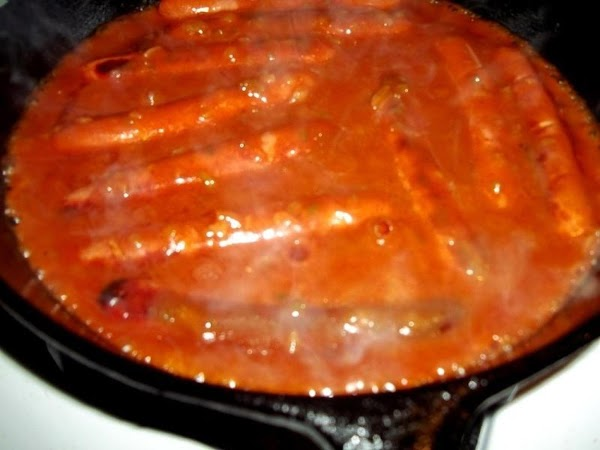 Pour sauce over dogs and simmer for 10 minutes. Moving hot dogs around to...