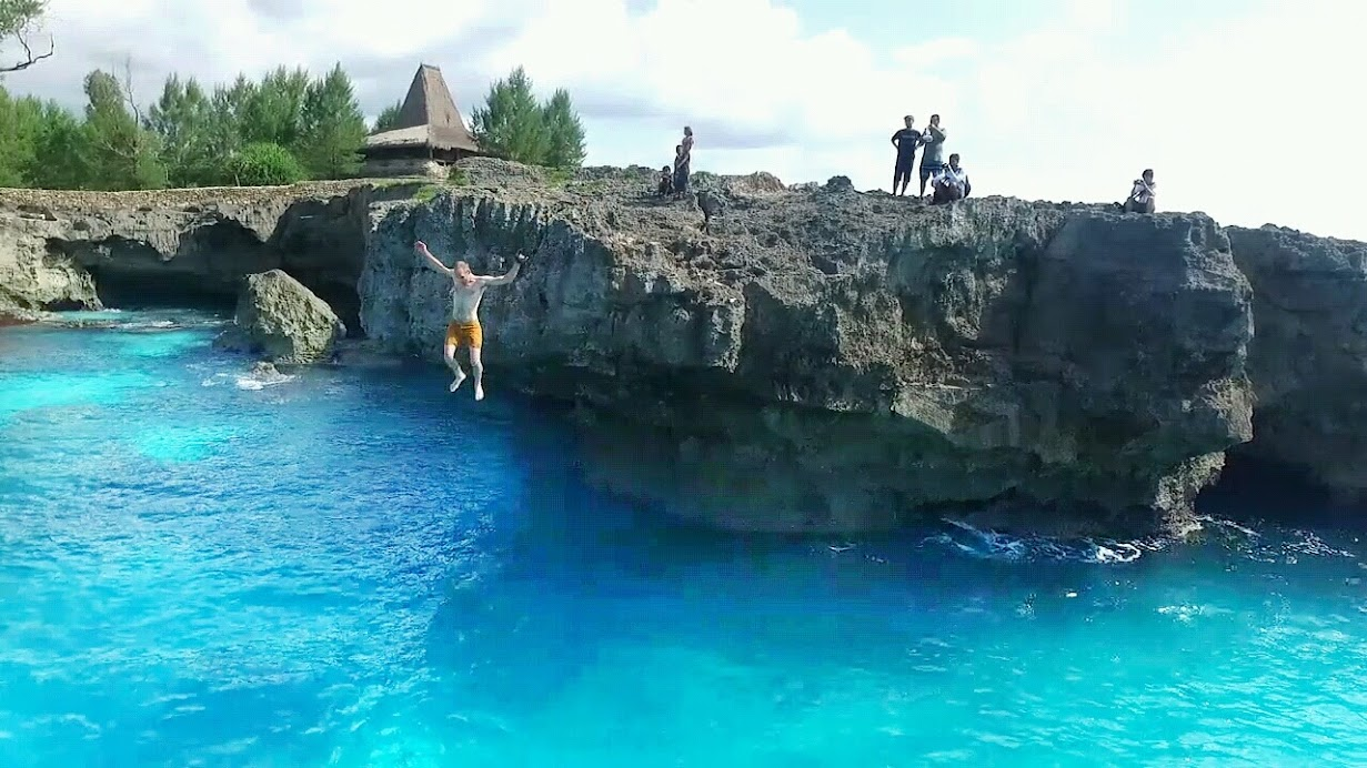 Cliff jumping into the turquoise water at Mandorak Beach