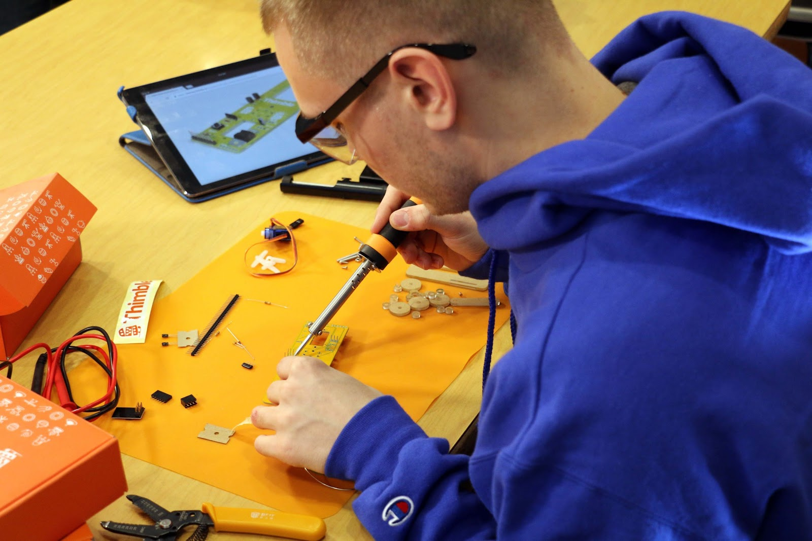 A boy in a blue sweatshirt and safety glasses sits at a table. He has a tablet that is open to the Thimble learning module as he builds a robotics project. An orange open Thimble box also sits on the table.