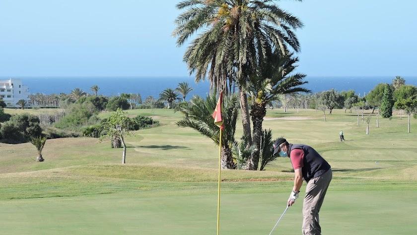 Un jugador patea en uno de los greenes del campo de golf de El Toyo.