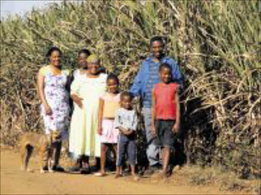 FROM NOTHING: Gladys Mkwhanazi (in the light green dress) with her family in Umbumbulu. PHOTO: SA Cane Growers' Association.