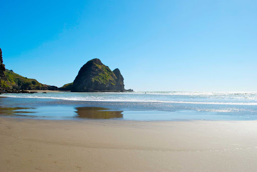 Piha-Beach-Auckland-with-surfer-in-distance - A view of Pina Beach in Auckland with a surfer in the distance.