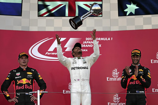 Riding high: Lewis Hamilton throws his winner's trophy as second-placed Max Verstappen, left, and third-place Daniel Ricciardo share the podium on Sunday. Picture: REUTERS