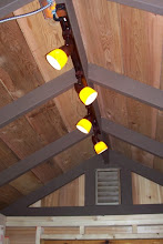 Photo: After the Super Bowl, I was surprised by my dad and husband with power! Nearing the end of our electrical wiring, the lights now work! :) I'm so happy with how they look! The last thing I need to do with these is to paint the silver conduit and junction box (upper left) brown to match the rafters.