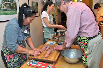 Photo: Karen and Lee rolling the sausages in tight logs