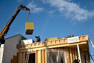 Photo: 20-11-2012 © ervanofoto Intussen gaan de werken op het dak verder. De kraanman brengt tussen twee ramen in nog even snel een pak isolatiemateriaal naar boven.