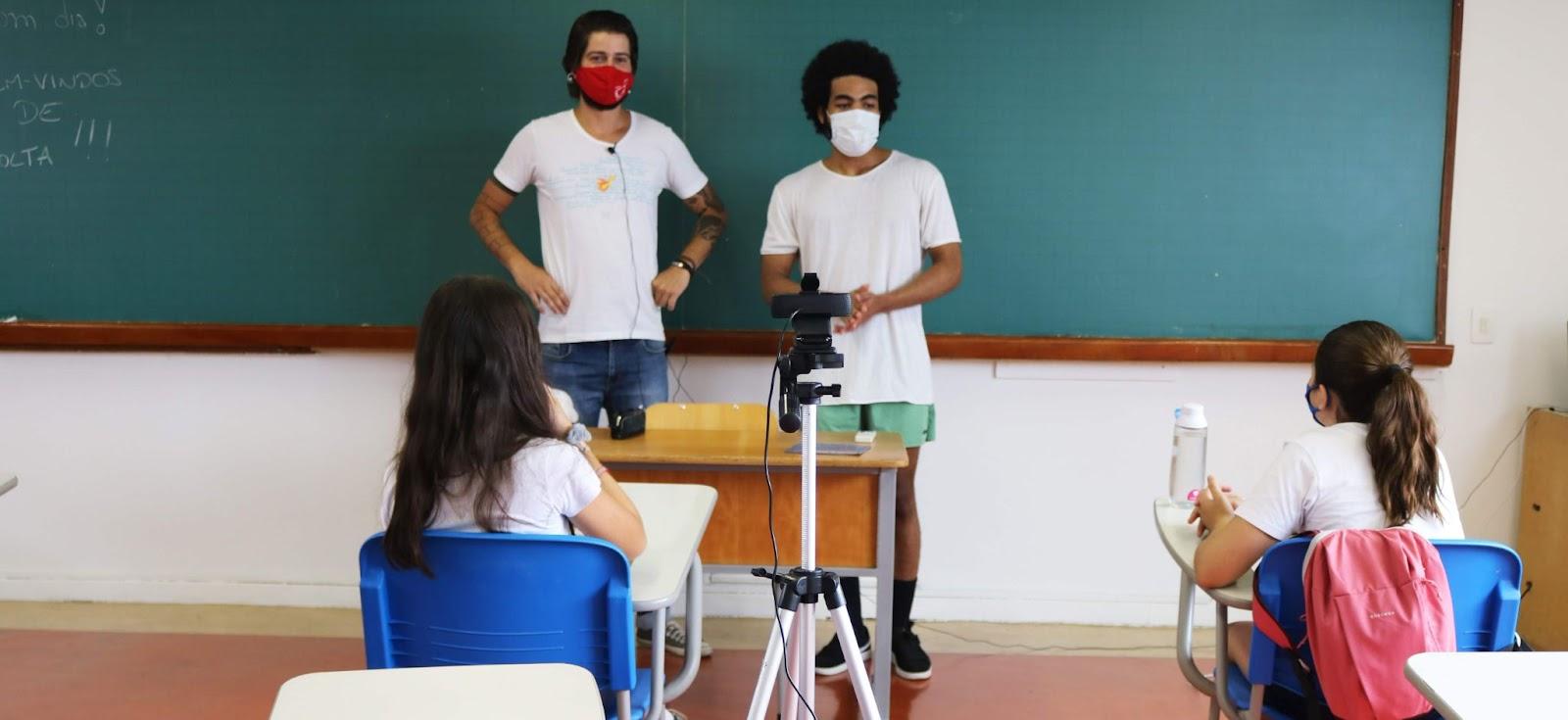 A imagem mostra uma sala de aula onde dois professores dão aula de máscara.