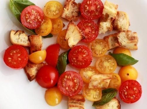 Slice tomatoes in half. Slice red onions, and tear basil leaves.Add to croutons, toss...