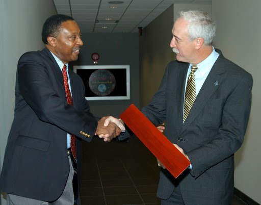 Former astronaut Winston Scott presents a NASA flag flown at the KSC Space Life Sciences Lab to NASA Administrator Sean O'Keefe.