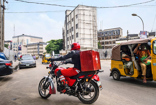 person on motorbike with a red health package attached to the back of the bike