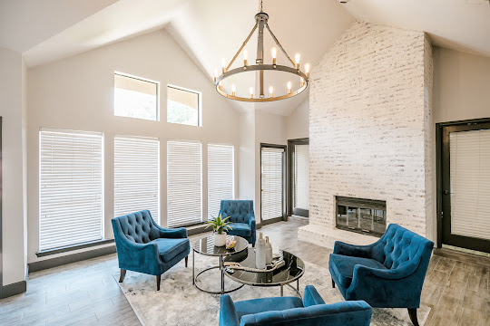 Interior clubhouse seating area with a modern chandelier, large windows, high ceilings, plush blue chairs, and a fireplace
