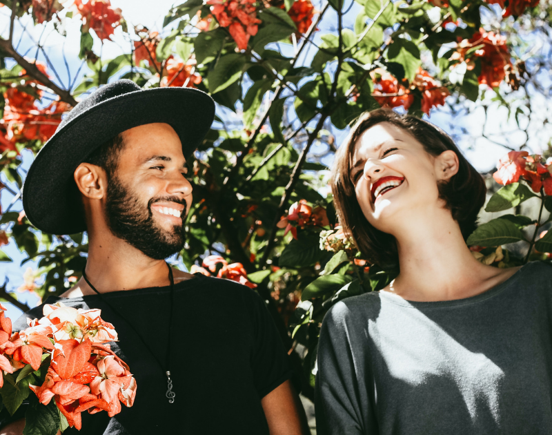 A man and a woman laughing underneath pretty red flowers