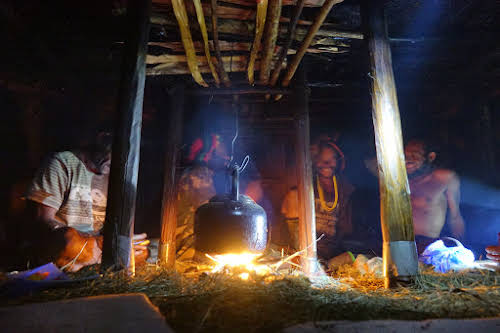 Indonesia. Papua Baliem Valley Trekking. Dinner time inside a traditional men's house in the Baliem Valley