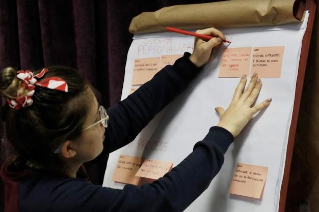 Mulher faz anotações em post its colados em flip chart