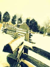 Photo: Old-fashioned photo of a wood fence and cabin in the snow at Carriage Hill Metropark in Dayton, Ohio.