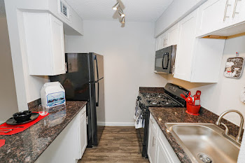 One Bed, One Bath Efficiency kitchen with black appliances and white cabinets