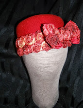 Photo: <KAPELUXE> Unique-Chique Hats by Luba Bilash ART & ADORNMENT  Tomato red wool felt base, double row of rosettes with rosette bow. 360 degree possibilities. Can also be worn on an angle. Size L - 56 cm/22 in $65 SOLD
