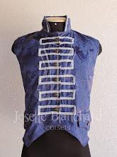Photo: Colete rococó curto em brocado azul escuro com aplicação de passamanaria prata. A partir de R$ 80,00.