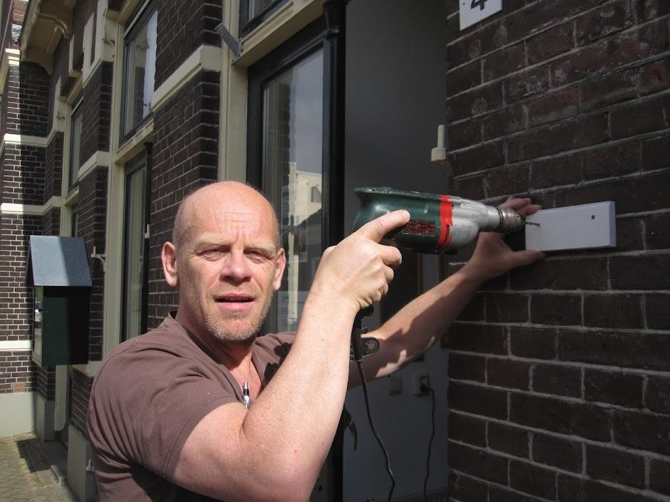 Buurttimmerman Henk monteert het infobord
