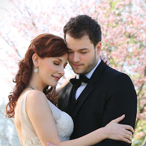 Bride and Groom Tenderly Embrace by Kim Wilson - Wedding Bride & Groom ( vertical, dreamy, photograph, exterior, people, spring, love, sunny, woman, lifestyle, intimate, embrace, pink, couple, gown, flowers, bride, man, black, cherry blossoms, male, white, romantic, image, adult, young, models, bridal, female, dress, wedding, outdoors, suit, beard, trees, bow, groom, outside )