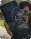 一個人手持智慧型手機,手機螢幕上顯示以文字轉語音功能創作的有聲書