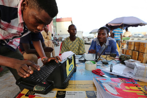 A man enters a customer's mobile cellphone sim card details on an MTN Group Ltd. registration machine at a roadside kiosk in Lagos. File photo: BLOOMBERG/GEORGE OSODI
