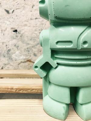 détail d'un robot en béton de couleur vert