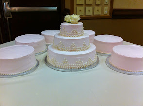 "Photo: 3-tier wedding cake w/six 14"" round sides cakes. Decor: light pink whipped cream frosting studded w/edible pearls."