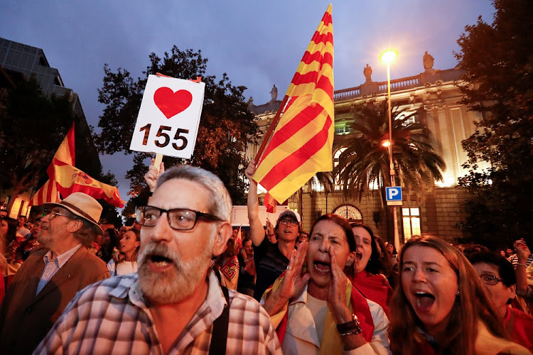 People shout holding Spanish and Catalan flags in Barcelona, Spain. Picture: REUTERS