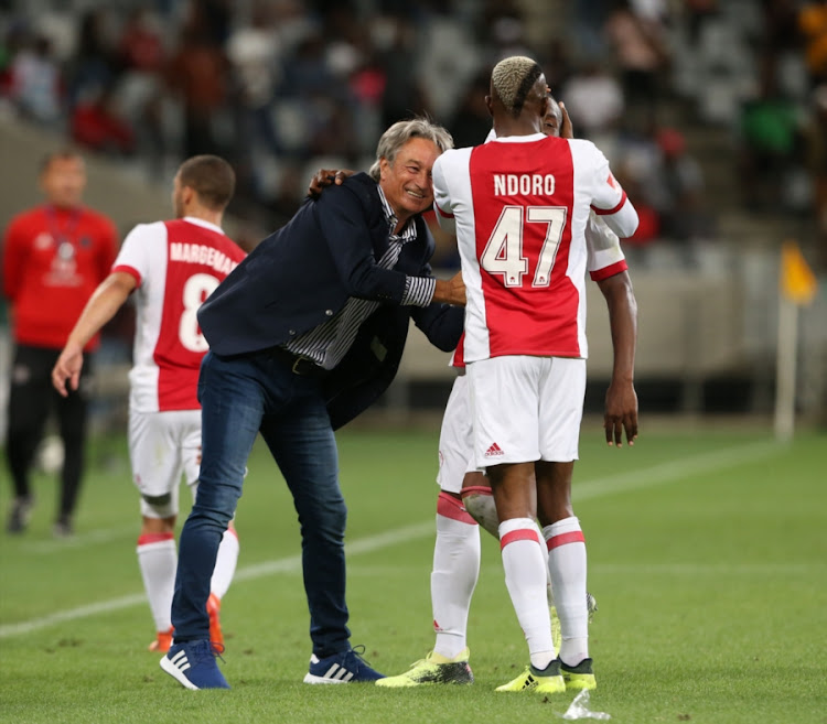 Ajax Cape Town players Tendai Ndoro and Yannick Zakri celebrate with head coach Muhsin Ertugral during the Absa Premiership match against Orlando Pirates at Cape Town Stadium on January 31, 2018 in Cape Town, South Africa.