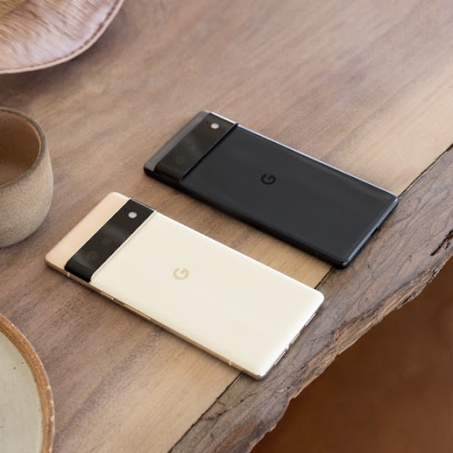 A Pixel 6 Pro and Pixel 6 sitting side by side on a wooden table top.
