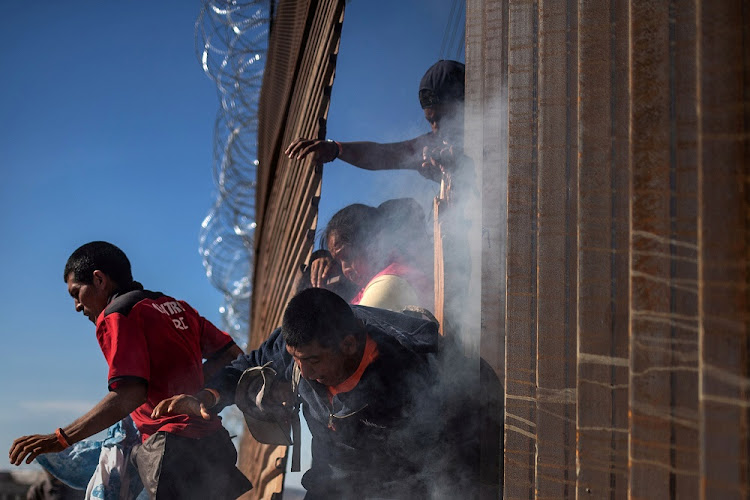 Migrants, part of a 'caravan' of thousands from Central America trying to reach the US, are forced back to Mexico by US Customs and Border Protection officials in Tijuana, Mexico, November 25 2018. Picture: REUTERS/ADREES LATIF