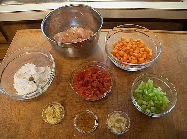Dice the chicken into bite-sized pieces. If you're using canned tomatoes, drain them; if you're...