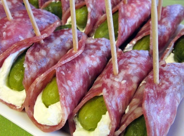 Spread each slice of salami with cream cheese, place pickle in the middle, roll...