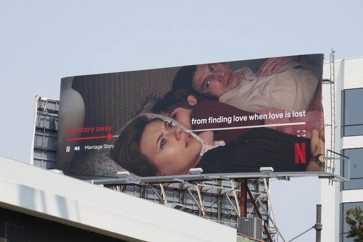 "A Netflix billboard with a woman crying and a man looking at her that says ""One story away... from finding love when love is lost."""