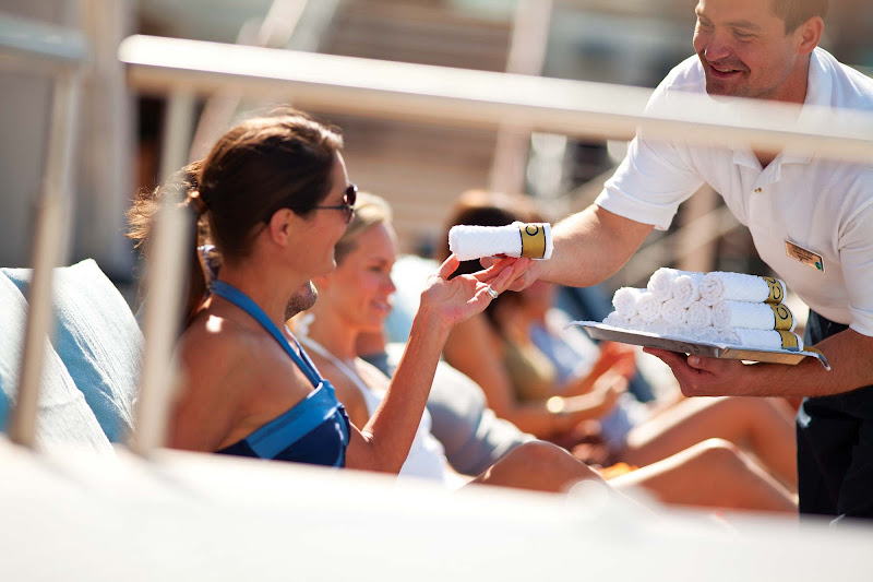 A pool butler provides a chilled towel to a guest on Celebrity Silhouette.